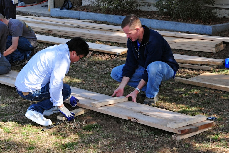 "Col. Ken ""Wolf"" Ekman, 8th Fighter Wing commander, and 8th FW Airmen build part of the retaining wall for ""Wolf Pack Garden"" in front of the Sonlight Inn, March 14, 2015, at Kunsan Air Base, Republic of Korea. The garden is part of a community initiative to promote healthy living for Wolf Pack Airmen. (U.S. Air Force photo by Capt. Reba Good/Released)"