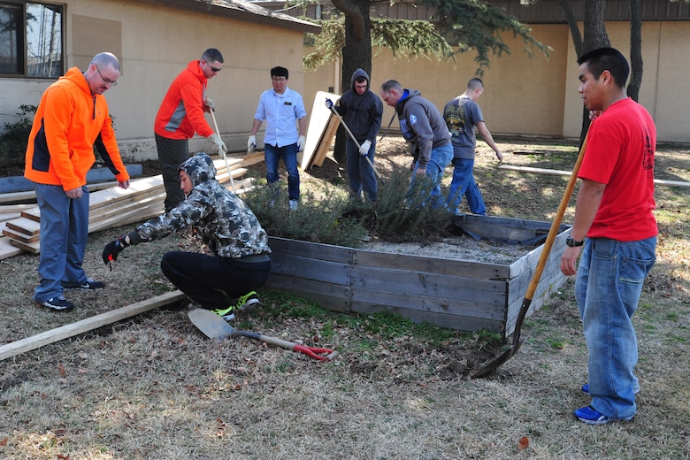 "8th Fighter Wing Airmen build the foundation for ""Wolf Pack Garden"" in front of the Sonlight Inn, March 14, 2015, at Kunsan Air Base, Republic of Korea. The garden is part of a community initiative to promote healthy living for Wolf Pack Airmen.  (U.S. Air Force photo by Capt. Reba Good/Released)"
