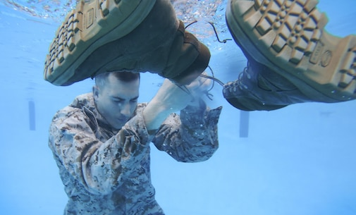 gt. Nicholas P. Slover, a U.S. Marine with the 26th Marine Expeditionary Unit, removes his boot before inflating his pants during a swim qualification course at the Area 5 pool aboard Marine Corps Base Camp Lejeune, N.C., March 17, 2015. Marines must tread water for 10 minutes during the qualification to demonstrate they can properly use their uniform as a flotation device for survival in water. (U.S. Marine Corps photo by Staff Sgt. Bobby J. Yarbrough/Released)