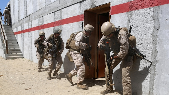 Marines with Charlie Company, 1st Reconnaissance Battalion, rush into a compound after breaching a door during a live-fire raid at Range 226 aboard Camp Pendleton, Calif., April 1, 2015. The company conducted the live-fire exercise as part of a predeployment workup in support of the 13th Marine Expeditionary Unit.