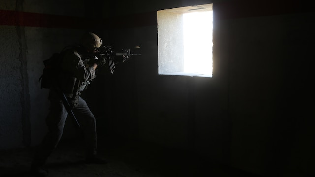 Sergeant Tahachee Appodaca, recon communicator, Charlie Company, 1st Reconnaissance Battalion, engages targets from inside a compound during a live-fire raid at Range 226 aboard Camp Pendleton, Calif., April 1, 2015. Appodaca, a native of Bakersfield, Calif., and the company conducted the live-fire exercise as part of a predeployment workup in support of the 13th Marine Expeditionary Unit.