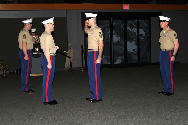 Sgt. Maj. John K. Wyatt (center right), incoming sergeant major of Marine Corps Recruiting Station Louisville, Kentucky, salutes Maj. Donald Hotchkiss, commanding officer of RS Louisville, before being handed the non-commissioned officers sword during an appointment, relief and retirement ceremony at the Kentucky Derby Museum, March 20, 2015.  The passing of the sword symbolizes the responsibility of the welfare of all Marines appointed under him. Wyatt reported for duty at RS Louisville after completing a tour as the First Sergeant of Drill Instructor School at Marine Corps Recruit Depot Parris Island. Wyatt replaced Sgt. Maj. Daniel G. Bullock who retired after 27 years of service. (Courtesy photo by Rachel Rosenblatt/Released)
