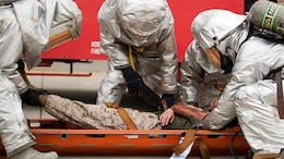 Aircraft Rescue Firefighters with Headquarters and Headquarters Squadron work together to evacuate a casualty during the mass casualty exercise aboard Marine Corps Air Station Iwakuni, Japan, April 3, 2015. MCAS Iwakuni conducted the exercise in preparation for the Japan Maritime Self-Defense Force/MCAS Iwakuni Friendship Day 2015 Air Show. The exercise simulated an aircraft crash and oil spill in a crowded area.