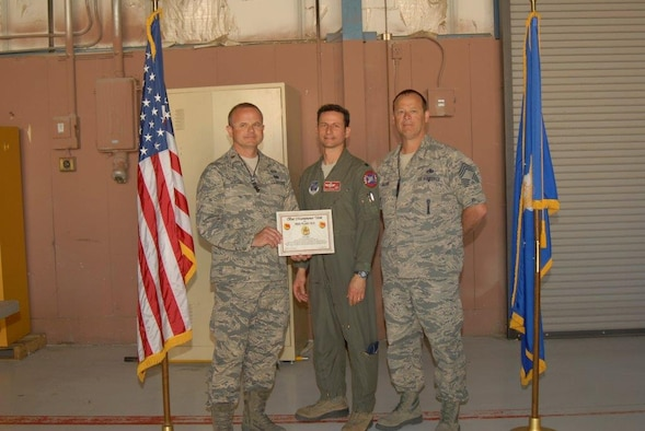 "Maj. Frank Horton (Left), 138th Maintenance Squadron, Lt. Col. Michael Scorsone (center), 125 Fighter Squadron Commander, and Chief Master Sgt. Brian Williams (right), 138th Maintenance Group, receive the ""Outstanding Maintenance Unit Award"", after completing Red Flag training at Nellis Air Force Base, Las Vegas, Nevada,  Mar. 12, 2015.  Red Flag is the Air Forces top air-to-air combat training exercise. (U.S. National Guard photo by Staff Sgt. Amber Hardison)"