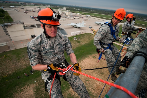 GOODFELLOW AIR FORCE BASE, Texas – Chief Master Sgt. of the Air Force James Cody, left, prepares to rappel down a 90-foot tower with Senior Airman Cody Carson, 312th Training Squadron firefighting student, center, and Chief Master Sgt. Thomas F. Good, 17th Training Wing Command Chief, right, at the Louis F. Garland Department of Defense Fire Academy April 3. Cody toured the fire academy and observed different aspects of fire protection training while visiting with staff and students. (U.S. Air Force photo/ Airman 1st Class Devin Boyer)