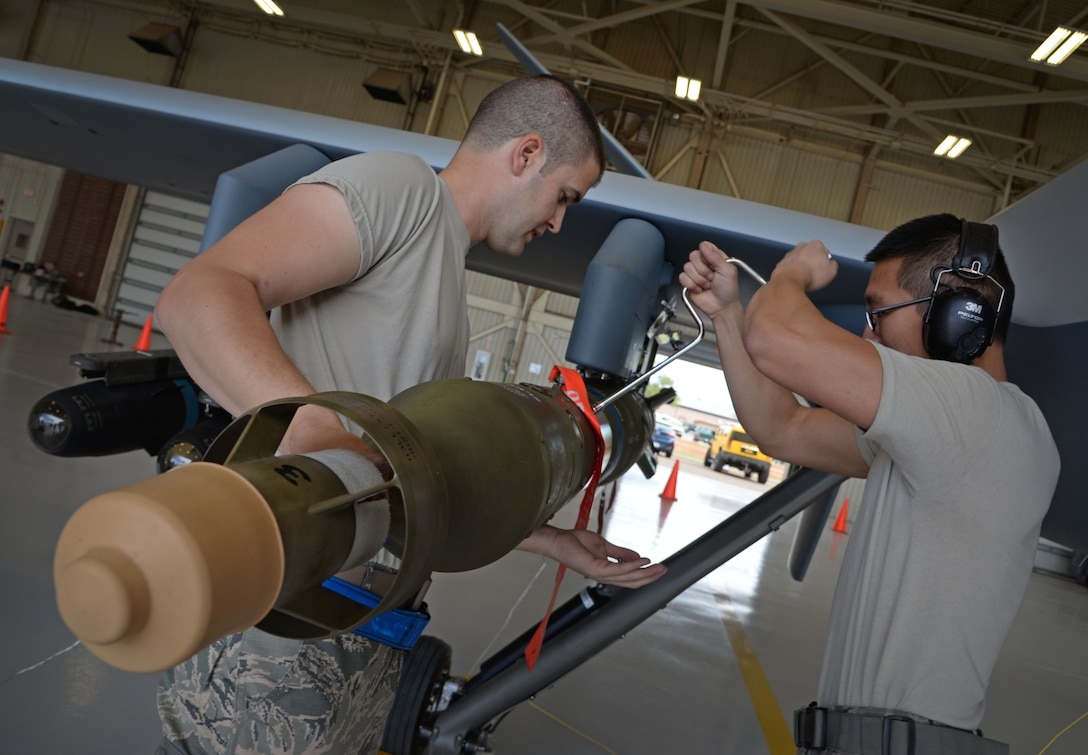 U.S. Air Force Senior Airman Josh Marion and Airman 1st Class Huy Diep, 27th Special Operations Maintenance Squadron MQ-9 Reaper and CV-22 Osprey armament shop, load inert weaponry on an MQ-9 during a load competition April 6, 2015 at Cannon Air Force Base, N.M. Weapons troops expertly loaded MQ-9 Reaper and AC-130W Stinger II platforms simultaneously, providing a real-time look into career field precision, while proving the depth of their unit's cohesion at the 27th SOW. (U.S. Air Force photo/Staff Sgt. Alex Mercer)