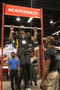 Sgt. Courtney Swinney, a Marine recruiter from Recruiting Station Orange County, observes as a National Society of Black Engineers career fair attendee participates in a Pull-up Challenge at the Marine Corps booth during the 2015 NSBE Convention March 27, 2015. Investing in a diverse and representative officer corps will help generate and sustain a future force that has cultural expertise, language skill sets and a variety of philosophies needed to meet operational requirements in the Marines. It was also an opportunity to reinforce the idea of the armed forces as viable career option within the African-American community.