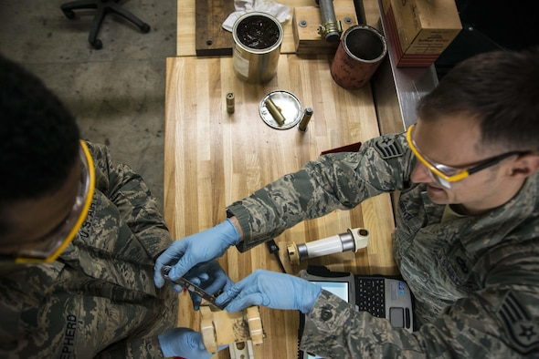 Senior Airman Rodney Shepherd and Staff Sgt. Brian Argenti, 35th Maintenance Squadron hydraulics systems maintainers, repair an F-16 Fighting Falcon's landing gear system March 31, 2015, at Misawa Air Base, Japan. As back shop maintainers, the duo repairs parts brought to them from crew chiefs on the flightline. Once a part is repaired, it is qualified for use on any F-16 across the Air Force. (U.S. Air Force photo/Staff Sgt. Derek VanHorn)