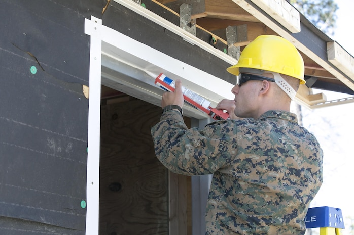 Cpl. Thomas Jenkins, a combat engineer with 8th Engineer Support Battalion, 2nd Marine Logistics Group, applies caulk to a door frame during a construction project aboard Camp Lejeune, N.C., March 31, 2015. Marines with 8th ESB built a storage facility for the unit's martial arts equipment as training for an upcoming deployment. The Marines will use the same skills to construct schools and other facilities overseas. (U.S. Marine Corps photo by Cpl. Elizabeth A. Case/Released)