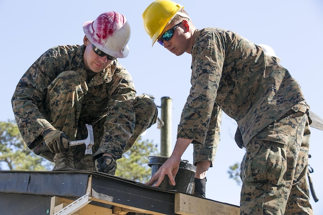 Marines with 8th Engineer Support Battalion, 2nd Marine Logistics Group, nail felt paper, a water-proofing and insulating material, to the roof of a building aboard Camp Lejeune, N.C., March 31, 2015. Engineers with 8th ESB built a storage facility for the unit's martial arts equipment as training for an upcoming deployment. The Marines will use the same skills to construct schools and other facilities overseas. (U.S. Marine Corps photo by Cpl. Elizabeth A. Case/Released)