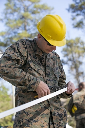 Lance Cpl. Donovan Perry, a combat engineer with 8th Engineer Support Battalion, 2nd Marine Logistics Group, trims J-channel, a material that provides a neat-looking trim for the vinyl siding of a building, aboard Camp Lejeune, N.C., March 31, 2015, during a construction project. Marines with 8th ESB built a storage facility for the unit's martial arts equipment as training for an upcoming deployment. The Marines will use the same skills to construct schools and other facilities overseas. (U.S. Marine Corps photo by Cpl. Elizabeth A. Case/Released)