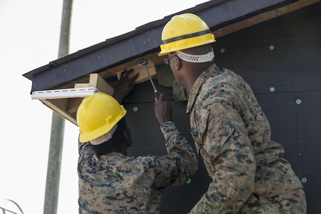 Cpl. Alatta Lawrence, left, and Lance Cpl. Thea Robertson, combat engineers with 8th Engineer Support Battalion, 2nd Marine Logistics Group, nail wood to the side of a building aboard Camp Lejeune, N.C., March 31, 2015. Engineers with 8th ESB built a storage facility for the unit's martial arts equipment as training for an upcoming deployment. The Marines will use the same skills to construct schools and other facilities overseas. (U.S. Marine Corps photo by Cpl. Elizabeth A. Case/Released)