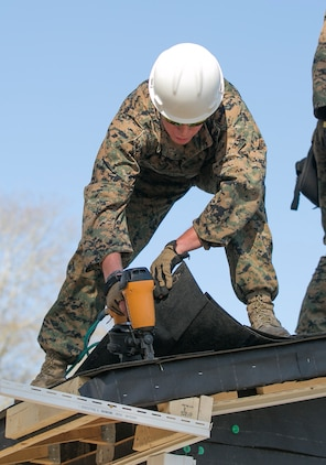 A combat engineer with 8th Engineer Support Battalion, 2nd Marine Logistics Group, nails shingles to the roof of a building aboard Camp Lejeune, N.C., March 31, 2015. Marines with 8th ESB built a storage facility for the unit's martial arts equipment as training for an upcoming deployment. The Marines will use the same skills to construct schools and other facilities overseas. (U.S. Marine Corps photo by Cpl. Elizabeth A. Case/Released)