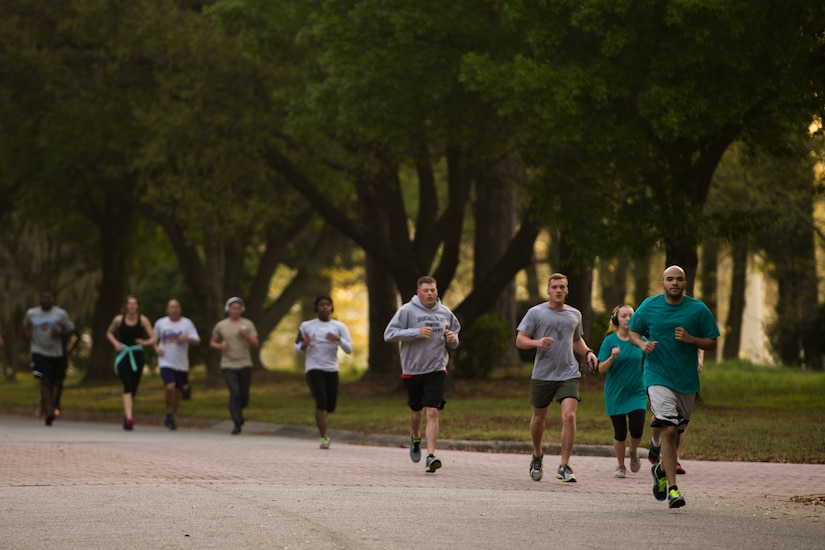 """Participants of the Joint Base Charleston Sexual Assault Awareness Month 5K run down a street April 4, 2015, on JB Charleston, S.C. The month of April has been declared the official SAAM for JB Charleston with a theme of """"Eliminate sexual assault: Know your part. Do your part."""" Events will be held throughout the month to help promote awareness.  (U.S. Air Force photo / Airman 1st  Class Taylor Queen)"""