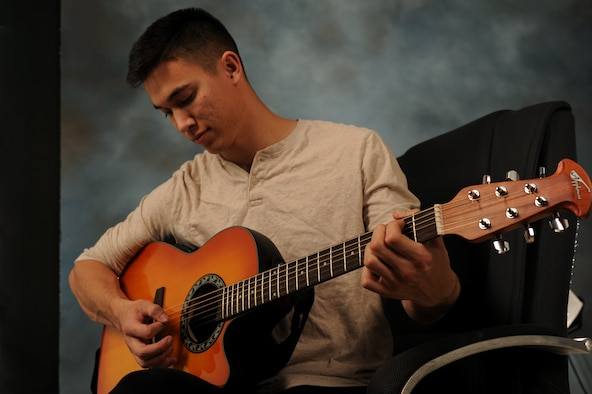 Airman 1st Class James Pratt, 28th Civil Engineer Squadron pavements and heavy equipment operator, plays acoustic guitar at Ellsworth Air Force Base, S.D., March 12, 2015.  Pratt was the number one selectee for vocal self-accompaniment during the 2015 Tops in Blue auditions, making him one of two Ellsworth Airmen selected for the entertainment unit's upcoming 2015 tour season. Following a 60-day training period, Pratt will join the group while they travel the world, providing entertainment to audiences in deployed locations, bases and local communities nationwide. (U.S. Air Force photo by Senior Airman Hailey R. Staker/Released)