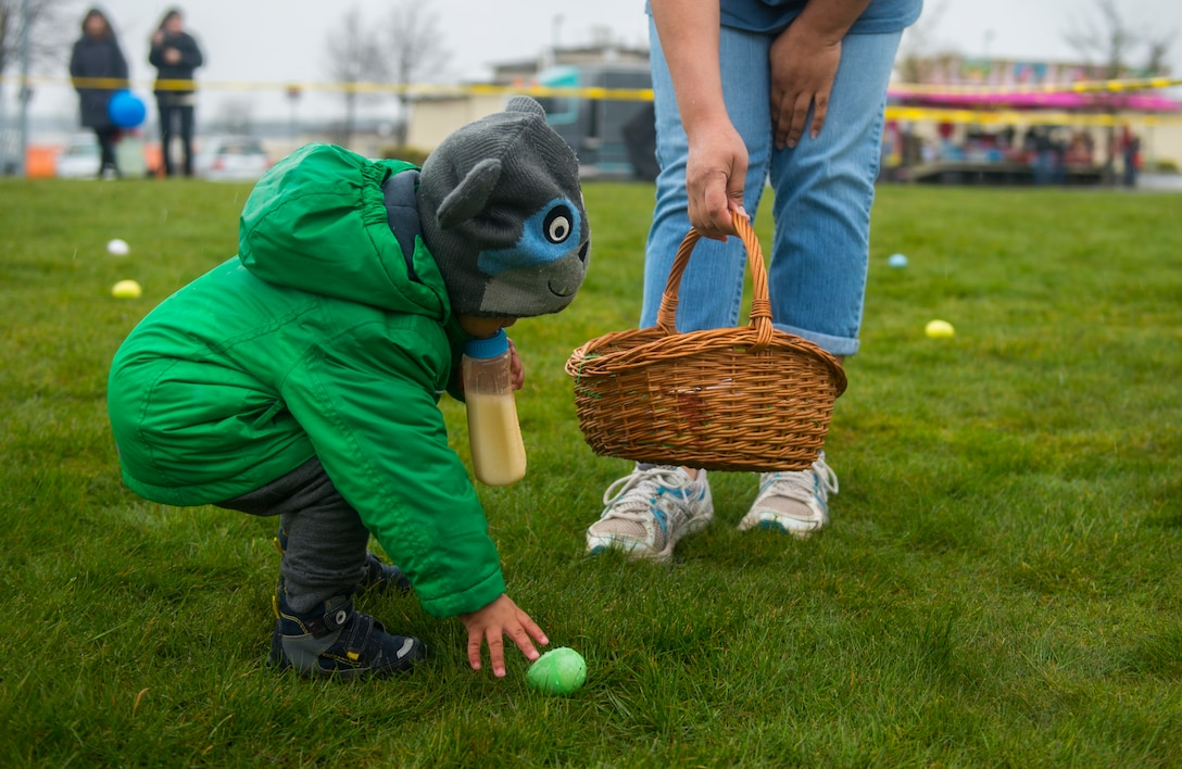 A child reaches for a plastic egg while participating in an Easter egg hunt on the grass field outside Club Eifel at Spangdahlem Air Base, Germany, April 4, 2015. Parents of children the ages 3 and younger could help in the egg hunt. (U.S. Air Force photo by Airman 1st Class Luke Kitterman/Released)