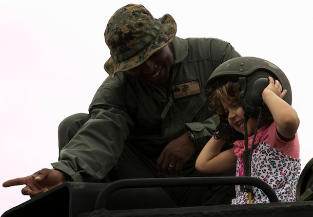 Cpl. Jude Exantus, right smiles with a service member's daughter on top of an Assault Amphibious Vehicle April 4 during a United Service Organization Easter celebration on Camp Schwab, Okinawa, Japan. Okinawa children and service members' children came together to participate in Easter activities, such as egg dyeing, making rabbit masks and an egg hunt. The Camp Schwab USO plans to organize this Easter celebration annually.  Exantus is a native of Ft. Lauderdale, Florida, and AAV crew chief with Combat Assault Battalion, 3rd Marine Division, III Marine Expeditionary Force.