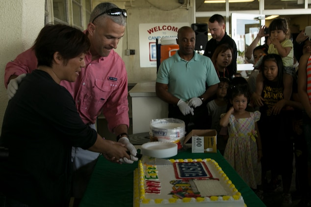 """Misako Shimabukuro, far left, and Col. David Odom cut the cake April 4 during a United Service Organization Easter celebration on Camp Schwab, Okinawa, Japan. """"One family, great friends,"""" said Odom, the commanding officer of Camp Schwab, as the cake was cut to share among service members, their families and Okinawa residents. The camp opened its gates to Henoko and Nago City residents to introduce them to Easter traditions that children in the United States participate in during the holiday.  Shimabukuro is a native of Henoko, Okinawa, and helped in organizing the Easter celebration.  Odom, a native of Hartsville, South Carolina, is the commanding officer of Camp Schwab and 4th Marine Regiment, 3rd Marine Division, III Marine Expeditionary Force."""