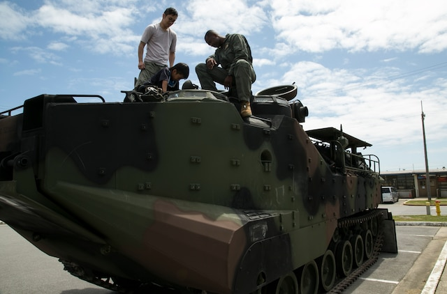 Cpl. Jude Exantus, right, showcases an Amphibious Assault Vehicle to an Okinawa family April 4 during a United Service Organization Easter celebration on Camp Schwab, Okinawa, Japan. The camp opened its gates to Henoko and Nago City residents to introduce them to Easter traditions that children in the United States participate in during the holiday. The Camp Schwab USO plans to organize this Easter celebration annually.  Exantus is a native of Ft. Lauderdale, Florida, and AAV crew chief with Combat Assault Battalion, 3rd Marine Division, III Marine Expeditionary Force.