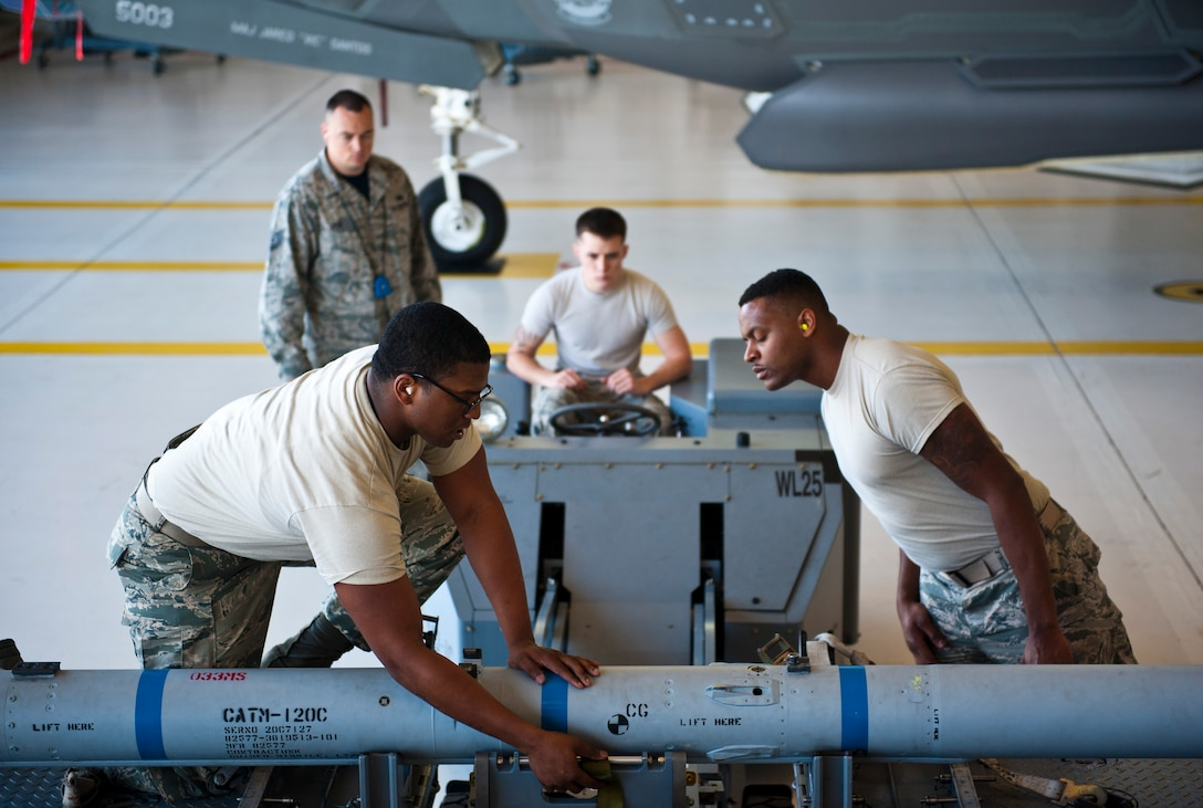 Staff Sgt. Timothy Gaulden, front left, 58th Aircraft Maintenance Unit crew six load crew chief, and Airman 1st Class John St. Cyr, 58 AMU crew six load crew member, guide an AIM-120 Advanced Medium-Range Air-to-Air Missile on to an MJ-1 lift truck during a weapons load competition on Eglin Air Force Base, Florida, April 3, 2015. During weapons load competitions, crews are evaluated on how well they load munitions safely, efficiently and in a timely manner as a team.  (U.S. Air Force Photo/Staff Sgt. Marleah Robertson)