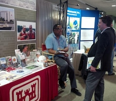 Gerald Rogers, public affairs specialist with the Norfolk District, talks about the Corps environmental mission with an attendee at the Virginia Environmental Symposium, April 1