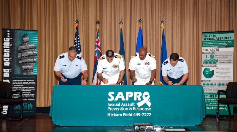 """Hawaii Air National Guard Brig. Gen. Braden Sakai, left, commander of the 154th Wing, Navy Capt. Mark Manfredi, chief of staff for Navy Region Hawaii, Navy Capt. Stanley Keeve Jr., commander of Joint Base Pearl Harbor-Hickam, and U.S. Air Force Col. Robert Cioppa, vice commander of 15th Wing, sign the Sexual Assault Awareness and Prevention Month (SAAPM) proclamation during an official ceremony at Hickam Memorial Theater at Joint Base Pearl Harbor-Hickam, April 2, 2015. This year's SAAPM theme is """"Eliminate sexual assault. Know your part. Do your Part."""" and focuses on bystander intervention. (U.S. Navy photo by Mass Communication Specialist 3rd Class Gabrielle Joyner/Released)"""