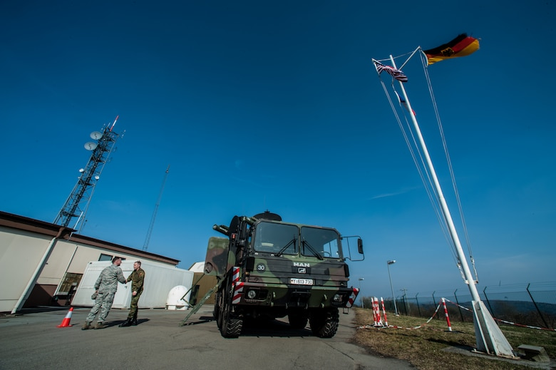 U.S. Air Force Col. Cloyce Adams, Polygone Warrior Preparation Center Detachment 3 commander, shakes hands with German army Master Sgt. Bernhard `Fledermausmann` Huetter, PWPC operator, next to a Roland surface-to-air missile at the Polygone Electronic Warfare Range in Bahn, Germany, March 18, 2015. Roland surface-to-air missiles offer a chance for pilots to train on live radar systems to prepare them for real-world scenarios. (U.S. Air Force photo/Senior Airman Nicole Sikorski)