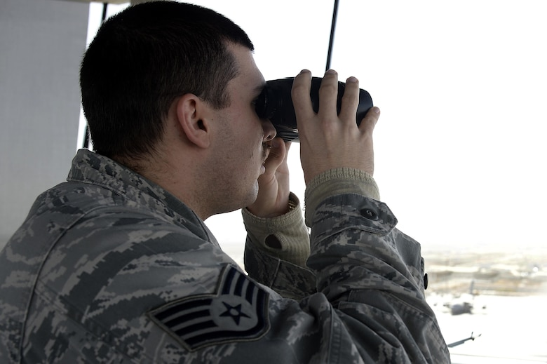 Staff Sgt. Matt, air traffic control liaison, scans the flightline from the air traffic control tower at an undisclosed location in Southwest Asia April 3, 2015. The duties of an air traffic controller liaison include making an automated terminal information service, which is a continuous broadcast of recorded weather and any other pertinent information for the pilots that they listen to before they go out. Matt is currently deployed from Tyndall Air Force Base, Fla. (U.S. Air Force photo/Tech. Sgt. Marie Brown/RELEASED)