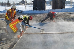 Contractors finish the surface of a concrete slab constructed with antifreeze concrete during a field demonstration at Fort Wainwright, Alaska, in March 2015. The air temperature was 14oF (−10oC).