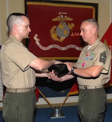 """Sgt. Maj. Kevin Conboy (right), sergeant major, Headquarters Group, Marine Corps Logistics Command, receives the American flag from Lt. Col. Adrian Cleymans, executive officer, Marine Depot Maintenance Command, and retiring official, during his retirement ceremony, April 9. The ceremony was held at Marine Corps Logistics Base Albany's Major S. P. """"Swede"""" Hansen Officers' Lounge."""