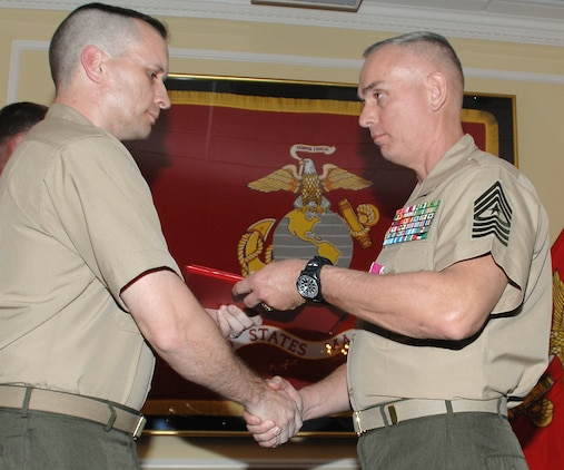 """Sgt. Maj. Kevin Conboy (right), sergeant major, Headquarters Group, Marine Corps Logistics Command, receives a certificate of retirement from Lt. Col. Adrian Cleymans, executive officer, Marine Depot Maintenance Command, and retiring official, during his retirement ceremony, April 9. The ceremony was held at Marine Corps Logistics Base Albany's Major S. P. """"Swede"""" Hansen Officers' Lounge."""