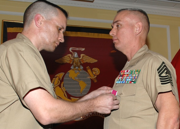 """Sgt. Maj. Kevin Conboy (right), sergeant major, Headquarters Group, Marine Corps Logistics Command, receives the Legion of Merit from Lt. Col. Adrian Cleymans, executive officer, Marine Depot Maintenance Command, and retiring official, during his retirement ceremony, April 9. The ceremony was held at Marine Corps Logistics Base Albany's Major S. P. """"Swede"""" Hansen Officers' Lounge."""