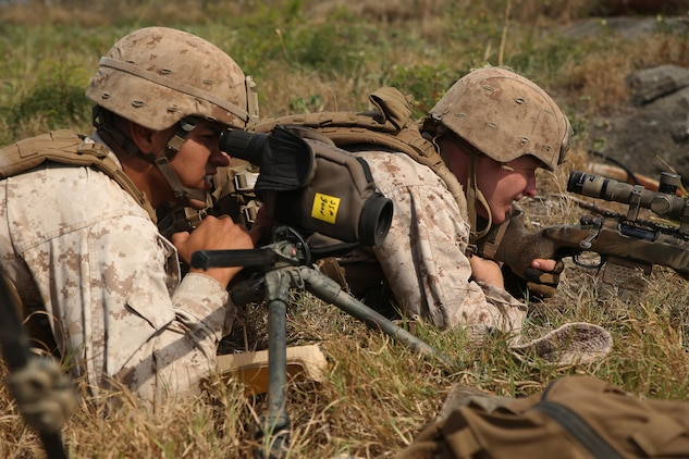 Cpl. Danny Villagomez (left) and Cpl. Evan Taylor, scout snipers with Weapons Company, 2nd Battalion, 3rd Marine Regiment, work as a team to hit a target as far as 850 yards away on top of Ulupau Crater at Range 10 aboard Marine Corps Base Hawaii April 8, 2015. The training was different from their typical flat-level or slight elevation ranges. The high angle is considered anything 30 degrees or greater.