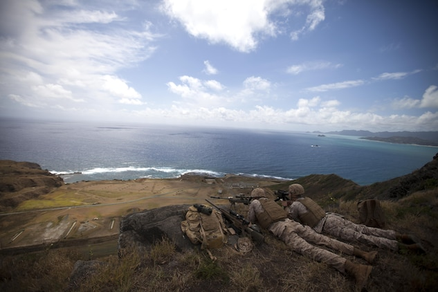 Scout snipers assigned to scout sniper platoon, 2nd Battalion, 3rd Marine Regiment, fire downrange at Range 10 aboard Marine Corps Base Hawaii, April 8, 2015. Marines improve their sniper proficiency by utilizing MCBH's natural resources to execute their training exercise. (U.S. Marine Corps photo by Lance Cpl. Julian Temblador, MCBH Combat Camera/Released)
