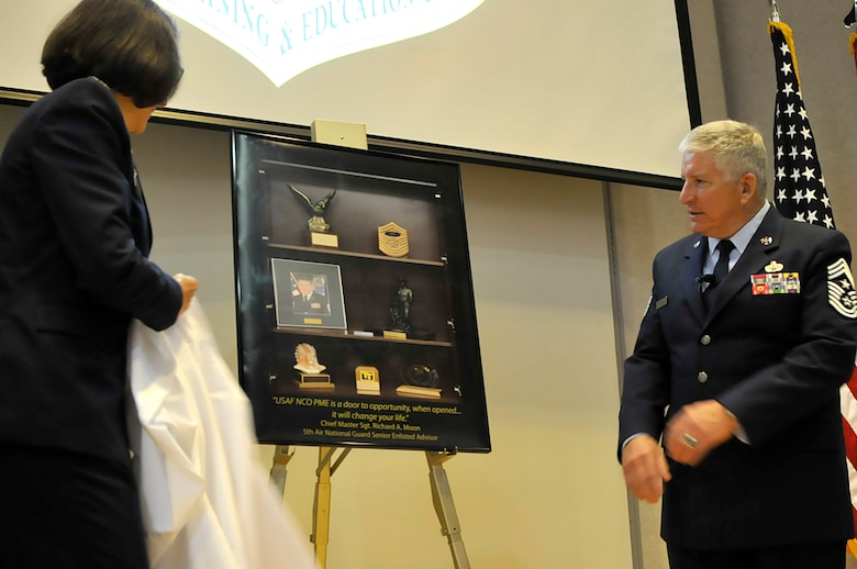 MCGHEE TYSON AIR NATIONAL GUARD BASE, Tenn. - Col. Jessica Meyeraan, commander of the I.G. Brown Training and Education Center, unveils a photograph of personal memorabilia here April 9, 2015, for retired Chief Master Sgt. Richard Moon during a ceremony naming building 412, Moon Hall. The photograph will be put on display there. Moon served 30 years in the military including time as TEC's commandant and as the fifth senior enlisted advisor to the Director of the Air National Guard. (U.S. Air National Guard photo by Master Sgt. Mike R. Smith/Released)