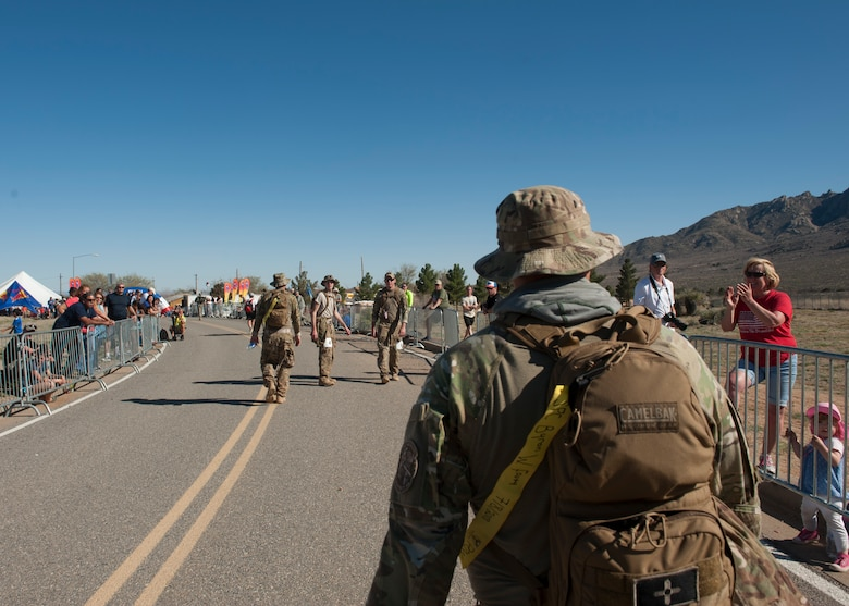 Tech. Sgt. Patrick Chavez, a 19th Logistics Readiness Squadron noncommissioned officer-in-charge of air terminal self-evaluation, closes in on the finish line at the Bataan Memorial Death March at White Sands Missile Range, N.M. March 22, 2015. The yellow ribbon Chavez carried on his bag represents a fallen service member. All of the members from the 19th LRS displayed a name on their gear. (U.S. Air Force photo by Airman 1st Class Scott Poe)