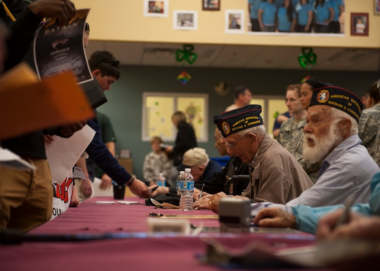 Some of the survivors of the Bataan Death March sign autographs during a meet and greet at White Sands Missile Range, N.M. The Bataan Memorial Death March serves as a reminder to today's generation of the harsh conditions the World War II veterans were forced to endure during their 60-mile march to a prisoner of war camp in the Philippines. (U.S. Air Force photo by Airman 1st Class Scott Poe)