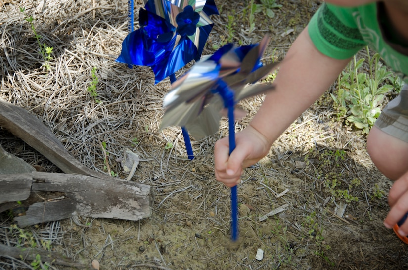 A child plants a pinwheel in the ground for Child Abuse Prevention Month on April 8, 2015 at the Karen Scott Heath Child Development Center on Joint Base Charleston – Weapons Station, S.C. Pinwheel gardens represent the effort to focus on community activities that support families and public policies prioritizing prevention of  child abuse and neglect. (U.S. Air Force photo/Staff Sgt. AJ Hyatt)