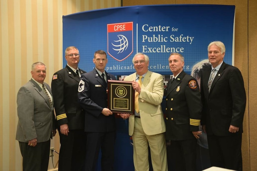 Glenn Easterby, Joint Base Charleston deputy fire chief; Greg Russell, JB Charleston assistant fire chief; Chief Master Sgt. David Rose, JB Charleston fire chief; Steve Westermann, Center for Public Safety Excellence, Inc., chairman; James Copeland, JB Charleston deputy fire chief; and Jim Podolski, Air Force fire chief,  pose with the plaque the  JB Charleston Fire Department earned when the Commission on Fire Accreditation International panel approved their accreditation at the Caribe Royale Hotel and Convention Center near Orlando, Fla., March 15, 2015.    (U.S. Air Force photo/Tech. Sgt. Mike Meares)
