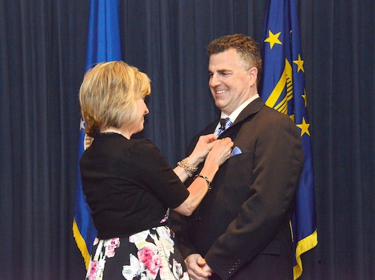 Mary Cooley pins on her husband, Thomas, the insignia of his new designation as an ST, or scientific professional. It is the highest rank a technical leader can achieve, considered to be the civilian equivalent of general. (Photo by Dennis Carlson)