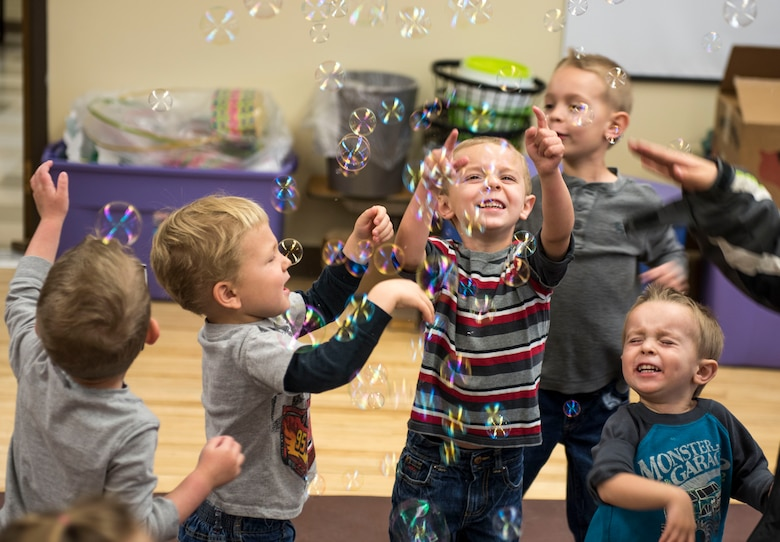 Children play with bubbles during the Sensory Camp at Mountain Home Air Force Base, Idaho, March 25, 2015. The Exceptional Family Member Program hosted the camp at the Youth Center to give children the opportunity to interact with one another and experience a variety of sensations of objects and textures. (U.S. Air Force photo by Airman 1st Class Jeremy L. Mosier/Released)