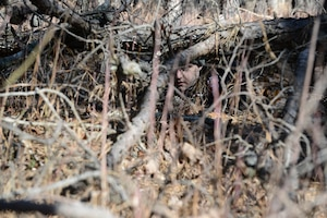 Senior Airman Adam Kwietniak, 6th Airlift Squadron loadmaster, hides while evading through the woods during a Survival, Evasion, Resistance and Escape exercise on Joint Base McGuire-Dix-Lakehurst, N.J., March 18, 2015. The exercise consisted of four air crew members evading a reaching an extraction point. (U.S. Air Force photo by Airman 1st Class Joshua King/Released)