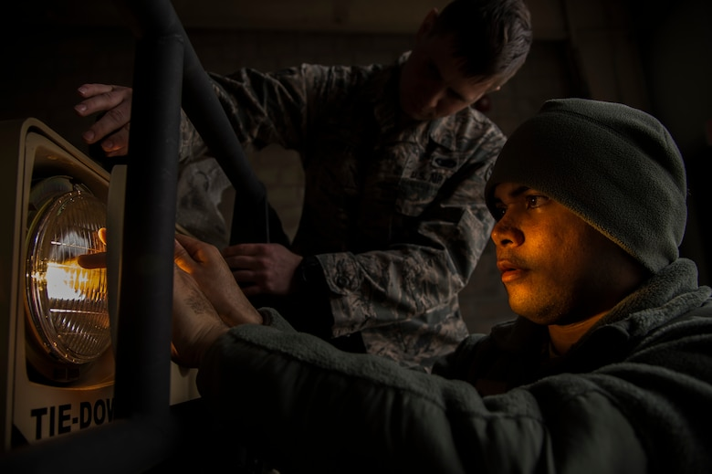 Senior Airman Christopher Good replaces a headlight on a vehicle as Senior Airman James Griffin helps hold it in place during the Devil Raid Mobility Exercise competition at Joint Base McGuire-Dix-Lakehurst, N.J., March 31, 2015. The 570th and 571st Contingency Response Groups stationed at Travis Air Force Base, Calif., are both scheduled to conduct their mobility exercise competition April 27. The Airmen are assigned to the 818 Contingency Response Group. (U.S. Air Force photo/Staff Sgt. Gustavo Gonzalez)