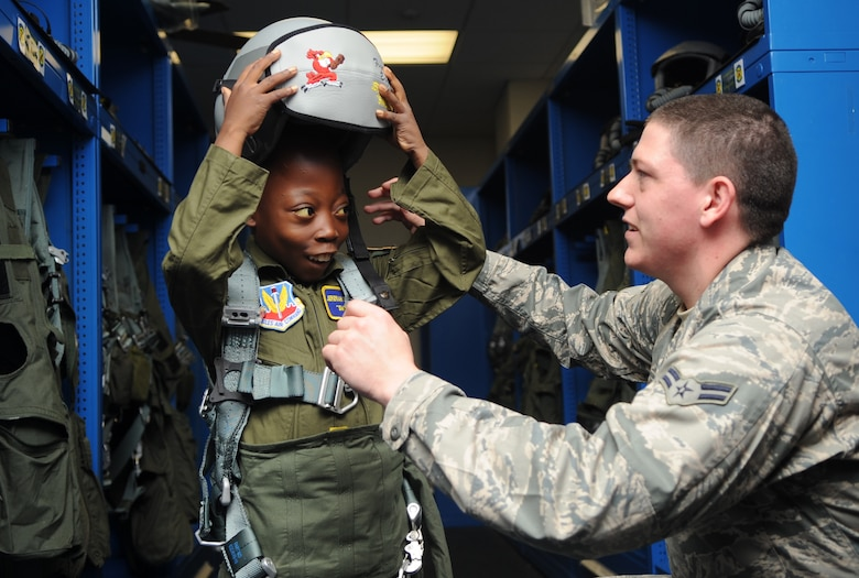 "Airman 1st Class Luke Locken fits Jeremiah Seaberry with flight gear during a 4th Fighter Wing Pilot for a Day event, April 3, 2015, at Seymour Johnson Air Force Base, N.C. PFAD organizers chose the call sign ""Swoosh"" for Seaberry as an allusion to his admiration for his favorite basketball player, Lebron James. Loken is a 4th Operations Support Squadron aircrew flight equipment technician. (U.S. Air Force photo/Senior Airman Ashley J. Thum)"