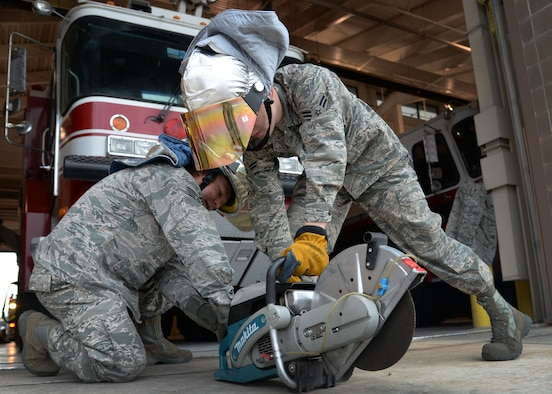 U.S. Air Force Staff Sgt. Joseph Peterson and Airman 1st Class Tyler Foster, 27th Special Operations Civil Engineer Squadron firefighters, ops check a high-power saw April 8, 2015 at Cannon Air Force Base, N.M. The K-12 is used to cut through aircraft in the event of emergency aircrew extraction. (U.S. Air Force photo/Staff Sgt. Alex Mercer)