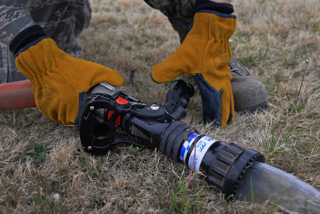 U.S. Air Force Airman 1st Class Tyler Foster, 27th Special Operations Civil Engineer Squadron firefighter, removes the main nozzle from a hose following ops checks April 8, 2015 at Cannon Air Force Base, N.M. Cannon's fire protection crew tests all essential equipment following morning roll call. (U.S. Air Force photo/Staff Sgt. Alex Mercer)