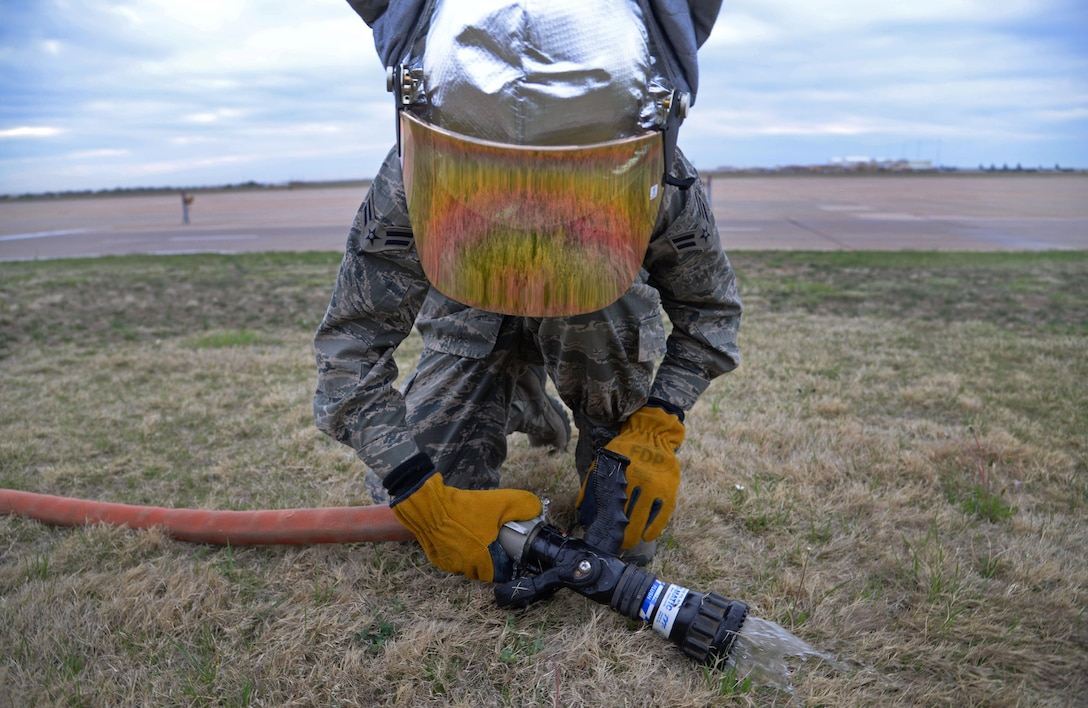 U.S. Air Force Airman 1st Class Tyler Foster, 27th Special Operations Civil Engineer Squadron firefighter, detaches the main nozzle from a hose after ops checks April 8, 2015 at Cannon Air Force Base, N.M. Cannon's fire protection crew must inspect and tests all essential equipment following morning roll calls. (U.S. Air Force photo/Staff Sgt. Alex Mercer)