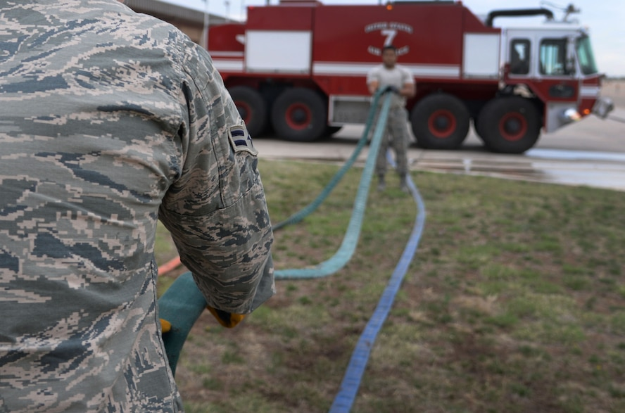 U.S. Air Force Airman 1st Class Tyler Foster and Staff Sgt. Rodney Welch, 27th Special Operations Civil Engineer Squadron firefighters, untangle a fire hose after ops checks April 8, 2015 at Cannon Air Force Base, N.M. If the hose it stored properly, firefighters can more easily access the equipment in the event of an emergency. (U.S. Air Force photo/Staff Sgt. Alex Mercer)