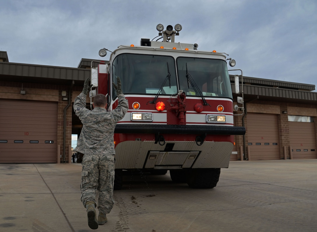 U.S. Air Force Staff Sgt. Joseph Peterson, 27th Special Operations Civil Engineer Squadron firefighters, helps guide a rescue engine back into its bay position April 8, 2015 at Cannon Air Force Base, N.M. Once crews have inspected and tested all equipment and vehicles, they are able to start other duties and training for the day. (U.S. Air Force photo/Staff Sgt. Alex Mercer)
