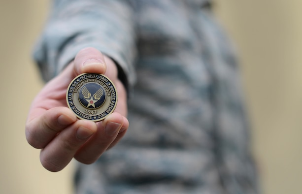 """The Airman's coin signifies the beginning of an enlisted member's career upon graduating basic military training. The original version of the Airman's coin featured an eagle clawing its way out of the coin with the words """"Aerospace Power"""" under it. The most recent coin replaced the eagle with the new Air Force symbol. (U.S. Air Force photo/Airman 1st Class Deana Heitzman)"""